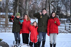 5 children in snow clothes holding up bird feeders in snow