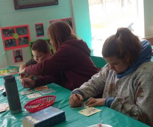 3 people working on an art project at table with green table cloth