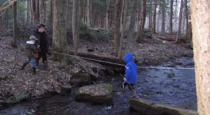 3 children crossing river in forest, wearing black and blue jackets